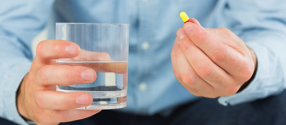 Man with medication and glass of water. Medication use. Medication adherence.